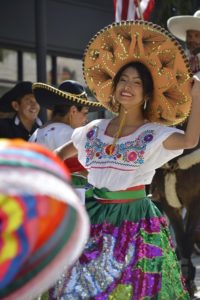 a woman in a sombrero, white blouse, and green/purple skirt